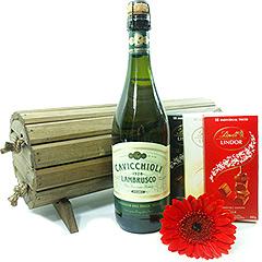 Um clássico baú de madeira escurecida reservando gratas surpresas - 3 tabletes Lindt, uma linda gérbera e um delicioso vinho italiano Lambrusco.
