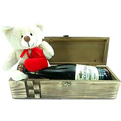 Um ursinho do amor, com um charmoso baú de madeira e um vinho italiano Lambrusco.
