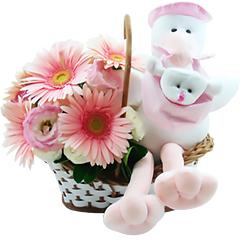 Uma delicada cestinha com flores em tons de rosa juntamente com uma simpática cegonha de pelúcia.