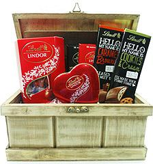 Deliciosa cesta Lindt contendo uma caixa de bombons Lindor, um coração com bombons e quatro diferentes tabletes Lindt.