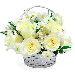 Delicada cesta de flores mistas e tons de branco.
