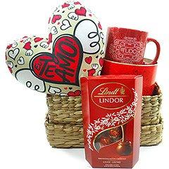 Deliciosos bombons lindor Lindt e cesta contendo um coração com os dizeres Te amo e caneca decorativa com motivo romântico.
