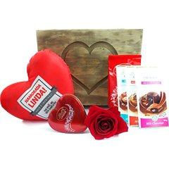 Um baú repleto de amor e delícias- três tabletes recheados Lindt, um pacote de bombons Lindor Lindt, um coração com bombons Lindt, uma rosa colombiana e uma almofadinha com os dizeres Namorada Linda.
