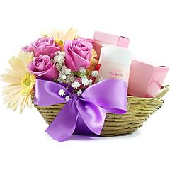 Uma delicada cesta contendo rosas e gérberas e um kit com dois produtos Natura - sabonetes e hidratante.
