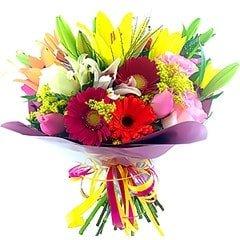 Belíssimo bouquet confeccionado com flores nobres coloridas. Gérberas, lírios, rosas importadas e nacionais, flores do campo de folhagens. Obs: Os lírios geralmente são entregues com as flores ainda em forma de botão de forma a durarem mais para o cliente.