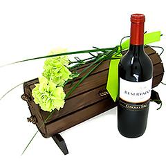 Uma composição clássica com um baú de madeira escurecida contendo um delicioso vinho tinto chileno e três magníficos cravos verdes.