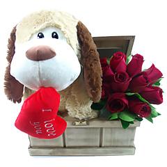 Lindo cachorrinho de pelúcia com um coração na boca e rosas vermelhas em um baú de madeira exclusivo.