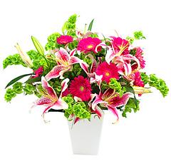 Maravilhosa composição com gérberas pink, lírios e folhagens em base de acrílico branca. Obs: Os lírios geralmente são entregues com as flores ainda em forma de botão de forma a durarem mais para o cliente.