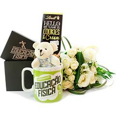 Uma caneca decorada com a profissão e um mini ursinho e barra de chocolate Hello Lindt, juntamente com um pequeno apanhado de flores em tons de branco. Presente original e encantador!