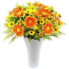 Um arranjo campestre de gérberas e flores do campo e folhagens em vaso de acrilico.