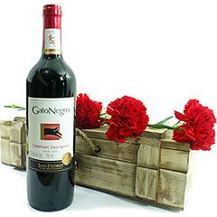 Lindos cravos vermelhos adornando um baú de madeira com um delicioso vinho tinto Cabernet Sauvignon Gato Negro.