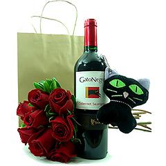 Um delicioso vinho tinto chileno Gato Negro, com um chaveiro de pelúcia de gatinho e um bouquet com rosas nacionais vermelhas.
