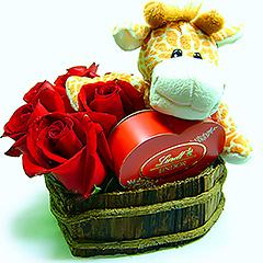 Uma simpática girafinha de pelúcia abraçada a uma caixa coração de bombons Lindt em base de madeira com rosas importadas vermelhas.