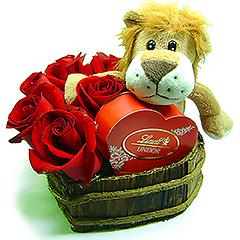 Um pequeno e charmoso leãozinho de pelúcia abraçado com uma caixinha de bombons Lindt em formato de coração em uma base de coração  de madeira com rosas vermelhas importadas.
