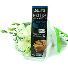 Um delicioso chocolate importado Lindt acompanhado de um bouquet de flores mistas brancas.