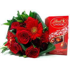 Impactante profusão de flores em tons de vermelho e um delicioso chocolate importado Lindt ao leite, conferem a esta composição um toque romântico para você presentear