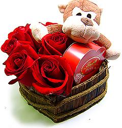 Um pequeno e simpático macaquinho com carinha sapeca, trazendo uma caixa coração de bombons Lindt e diversas rosas  vermelhas em um coração de madeira.