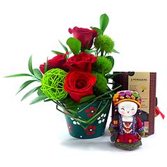 Um presente exclusivo e cheio de charme para expressar os mais nobres sentimentos. Aqui, a mensageira SHIMA (tradicional boneca chinesa produzida de forma totalmente artesanal) cultiva a Fortuna na alma das pessoas. Acompanha um vaso de cerâmica delicadamente pintado à mão, com sofisticada composição de rosas importadas e folhagens. Um presente exclusivo e cheio de charme para expressar os mais nobres sentimentos.
