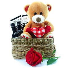 Uma exclusiva cesta romântica contendo dois vinhos tintos baby, dois tabletes de chocolate recheados importados Lindt, um ursinho de pelúcia apaixonado e uma rosa importada vermelha.