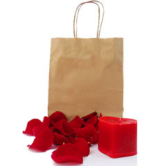 Um vela em formato de coração e pétalas vermelhas avulsas para decorar a cama.