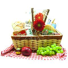 Uma cesta de pic nic com gérberas e repleta de  delicias - um bolo caseiro, um pacote de bolacha salgada,  dois pacotes de bolacha doce, polenguinho, dois sucos, dois achocolatados, pães de mel, croissant, duas geleias, duas frutas e uma charmosa toalha xadrez.