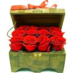 Um delicado báu de madeira repleto de rosas vermelhas tipo exportação e adornado com laço de cetim.