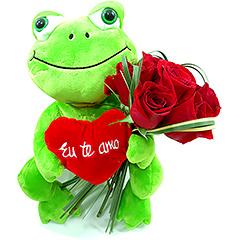 Alegre sapinho de pelúcia que carrega um apanhado de rosas  vermelhas