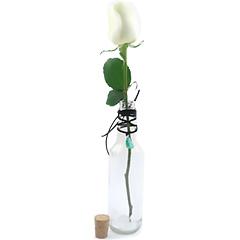 Uma original garrafa para uma linda rosa nacional branca solitária e um cordão com a pedra amazonita, que é uma pedra extremamente calmante, que tranquiliza o cérebro e o sistema nervoso, além de fortalecer a aura, alinhar o corpo físico e manter a saúde perfeita, representando o signo de touro.