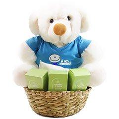 Comemore a chegada do bebê com um ursinho exclusivo Florencanto com a blusinha é um menino em uma cesta com quatro produtos da linha Mamãe e Bebê Natura.