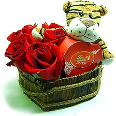 Solte as feras no momento de demonstrar o seu amor com esse tigrinho de pelúcia abraçado a uma caixa coração de bombons Lindt em base de madeira repleta de rosas vermelhas.