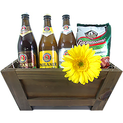 Três deliciosas cervejas Paulaner e dois snacks salgados e torradinhos para acompanhar, junto com uma gérbera natural em base de madeira.