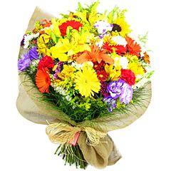 A explosão de cores das flores: lírios, lisianthus, gérberas, girassóis e flores do campo, cada qual contribuindo para a vivacidade e beleza desta composição.