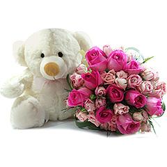 Delicado ursinho com laço rosa e um gracioso bouquet de rosas mistas em tons de rosa e pink.