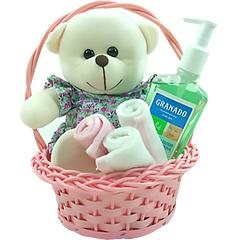 Graciosa ursinha de pelúcia com vestidinho em uma cestinha contendo um produto da linha Bebê da Granado e três Blankets (paninho de boca).