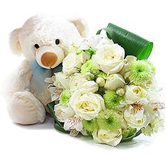 Delicado ursinho com laço azul e um bouquet de rosas e flores mistas em tons de branco e verde.