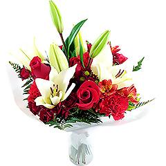 Flores mistas em tons de vermelho e branco em vaso de acrílico.
