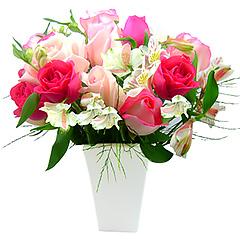Maravilhosas rosas nacionais com alstroemérias e folhagens em vaso de acrílico branco.