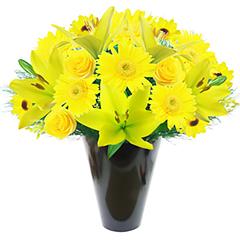 Lindo vaso com flores nobres em tons de amarelo - lirios, rosas e gérberas em meio à folhagens.