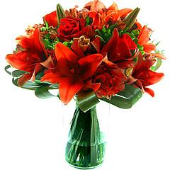 Belíssima composição com lírios,  alstroemérias importadas e rosas em tons de vermelho em base de acrílico adornado com folhagens.Obs: Os lírios geralmente são entregues com as flores ainda em forma de botão de forma a durarem mais para o cliente.