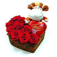 Um rústico coração de madeira repleto de rosas nacionais vermelhas, com uma girafinha de pelúcia e uma latinha coração de Bombons Lindor da Lindt.